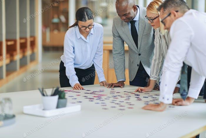 Diverse Geschäftsleute lösen gemeinsam ein Puzzle in einem Büro