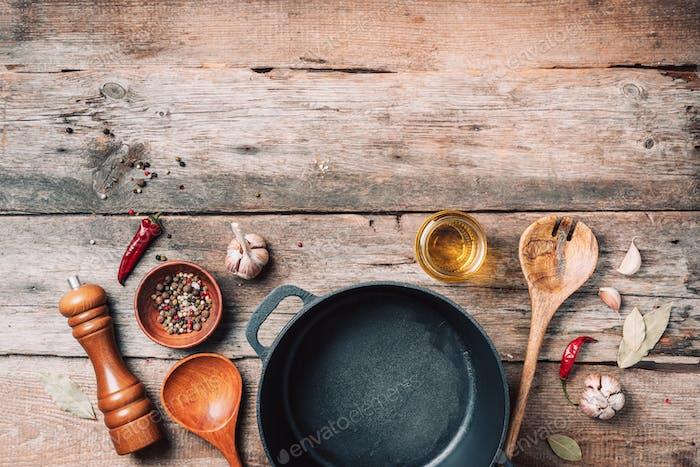 Gusseisen Topf, Gewürze, Pfefferstreuer, Fleischgabel, Öl, Gewürze auf Holzhintergrund. Draufsicht. Kopieren