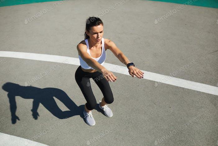Woman doing squat at stadium