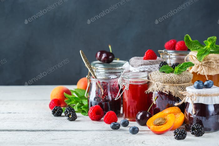 Assortment of seasonal berries and fruits jams in jars