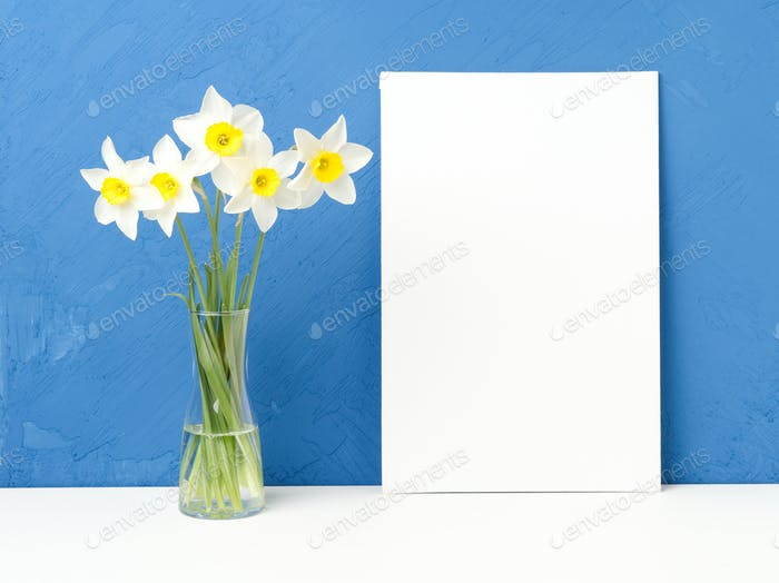 Bouquet of fresh flowers, blank white paper on white table, opposite blue textured concrete wall