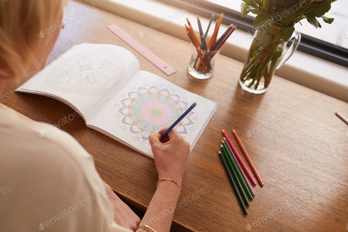 Woman drawing in colouring book for adults