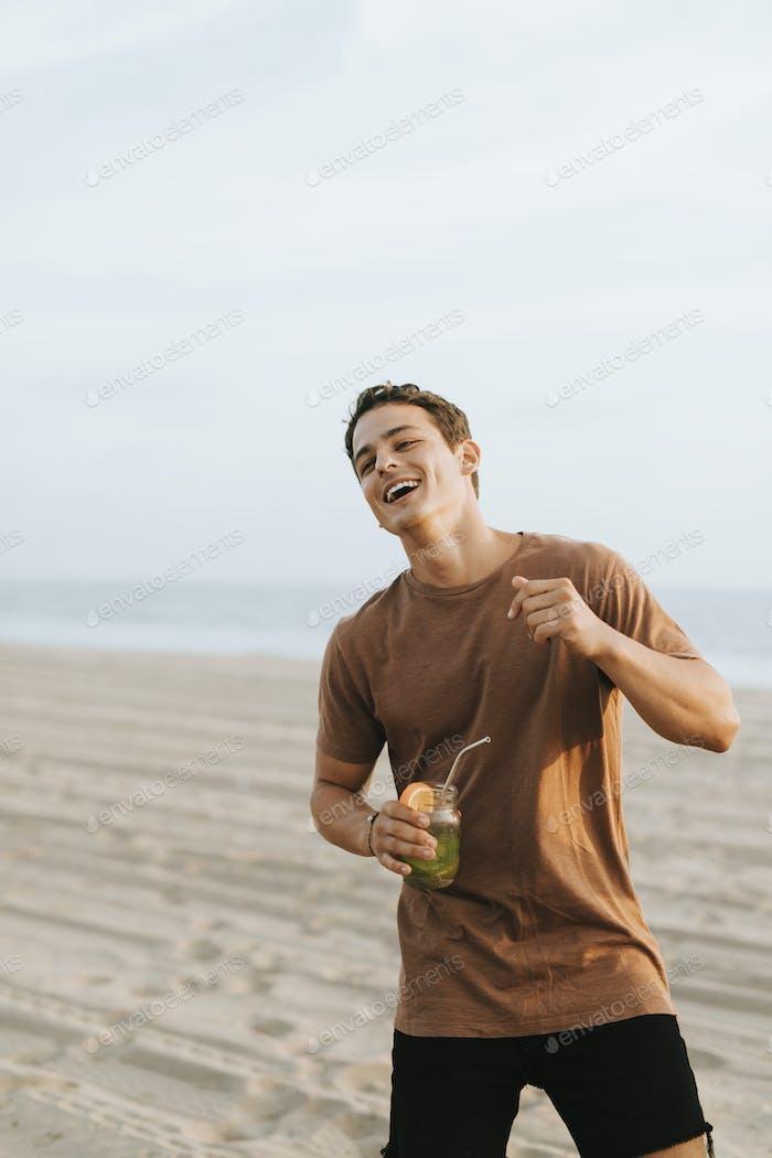 Mann trinkt einen Mojito auf einer Strandparty