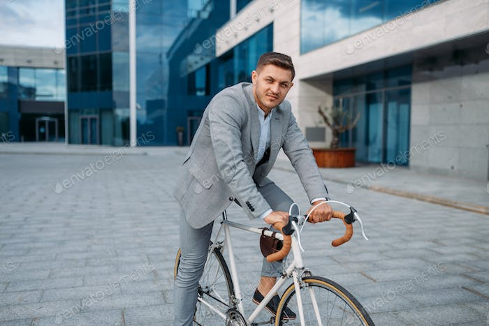 Young businessman in suit on bicycle in downtown
