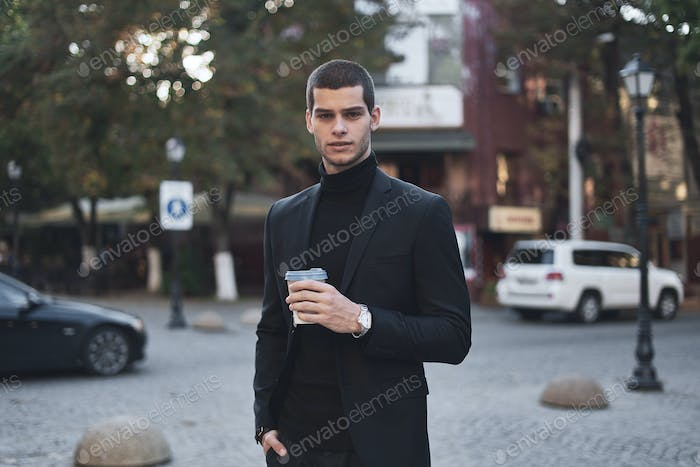 Young businessman going to the work with coffee