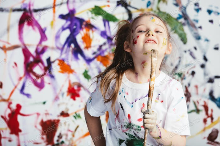 Young child painter standing with a brush