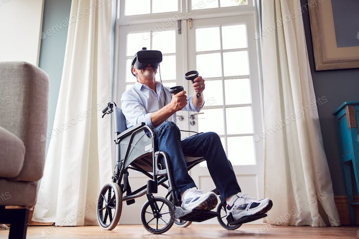 Mature Disabled Man In Wheelchair At Home Wearing Virtual Reality Headset Holding Gaming Controllers