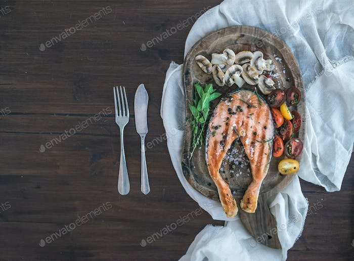 Grilled salmon steak with fresh herbs, roasted mushrooms, cherry