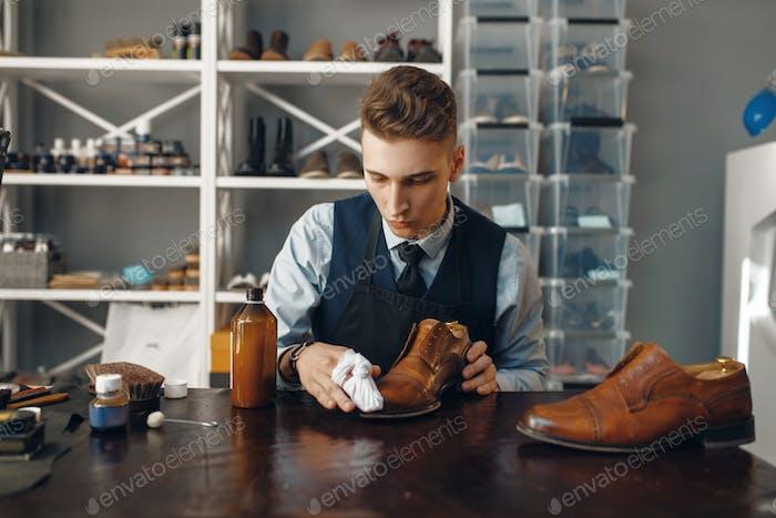Schuhmacher poliert den Schuh, Schuhreparatur
