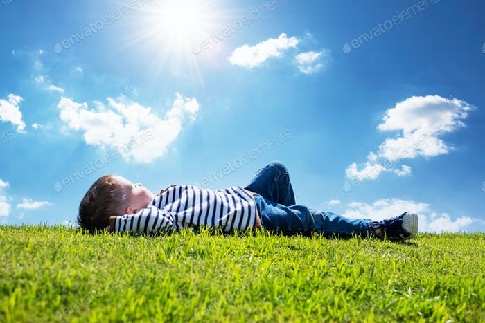 Happy little boy laying on green grass