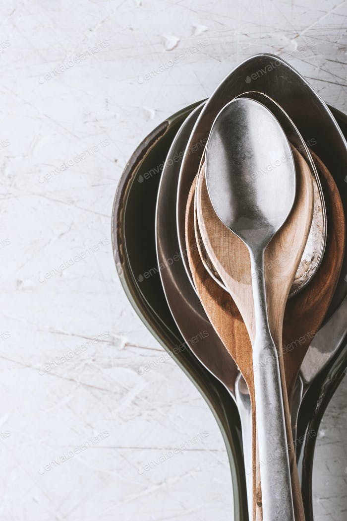 Different spoons on the  white table vertical