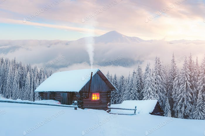 Fantastic winter landscape with wooden house in snowy mountains
