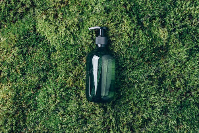 Unlabelled cosmetic bottle on green moss background. Biophilic design. Skin care, organic body