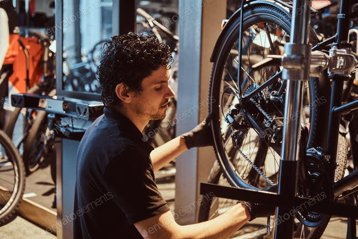 Attractive mechanic is fixing customer's bicycle at his own workshop.