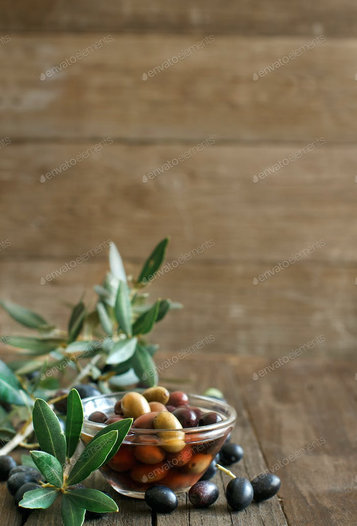 Fresh olives and olive branch on wood background