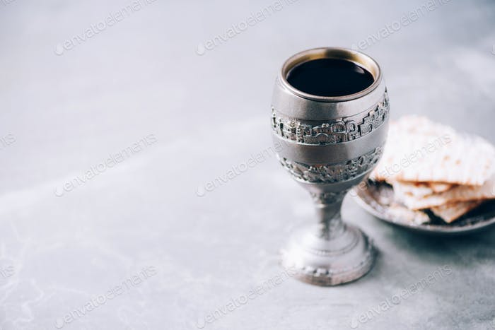 Jesish kiddush wine cup for passover with matzot, matzo bread. Pesah holiday. Banner with copy space