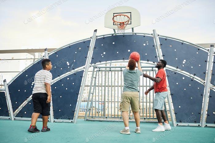 Throwing Ball Into Basketball Hoop