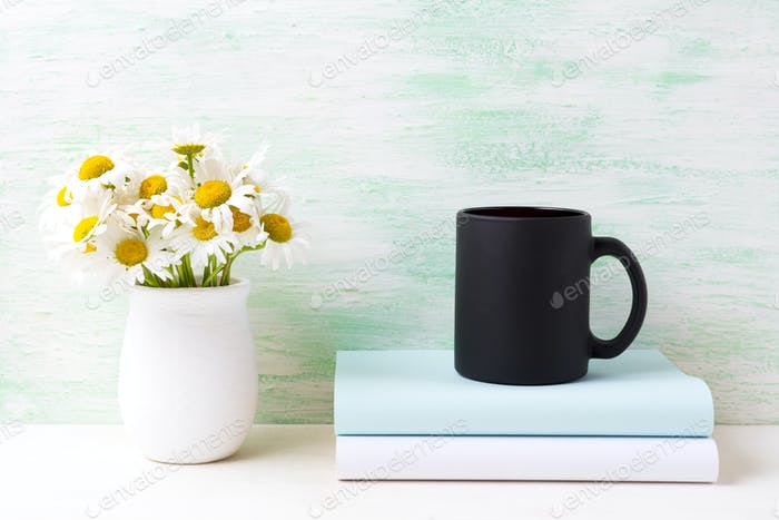 Black coffee mug mockup with white field chamomile bouquet in ha