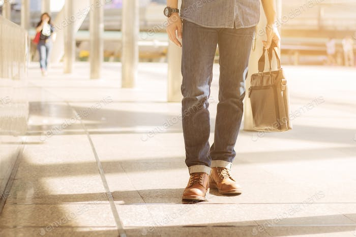 Man holding leather bag in city