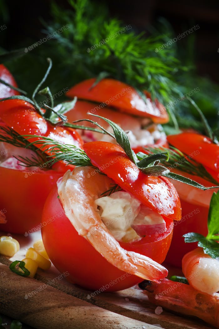 Tomatoes stuffed with shrimp meat and corn on a wooden plate