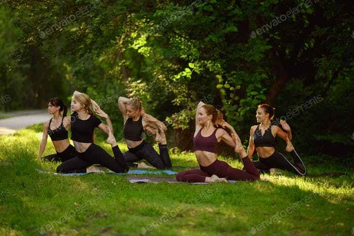 Women doing stretching exercise, yoga in park