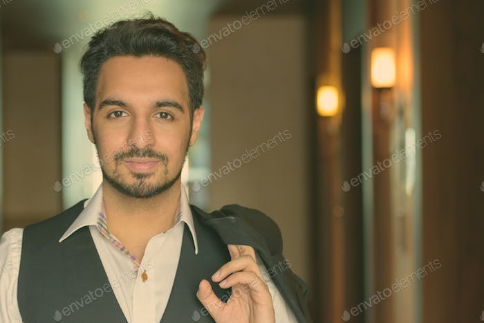 Young handsome Indian man holding jacket in the corridors of hotel