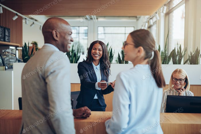 Smiling concierge helping two guests check in to a hotel