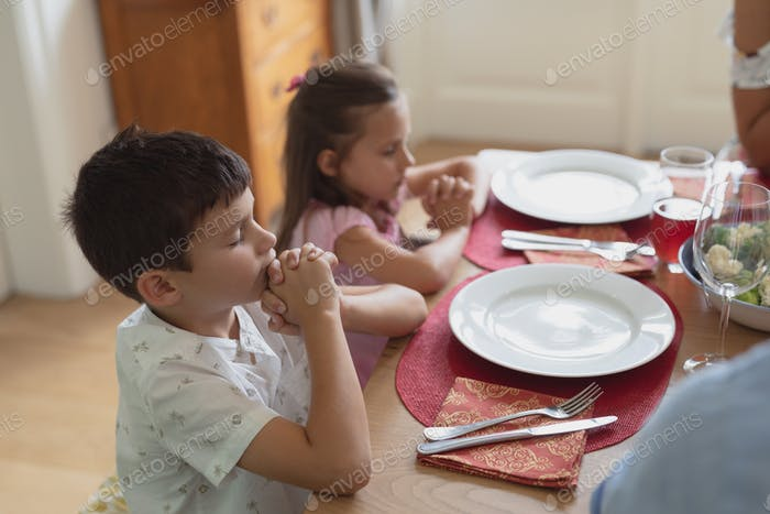 Caucasian family praying together before having lunch at dining table in comfortable home