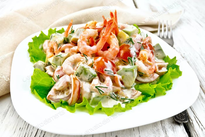 Salad with shrimp and tomato in plate on light board