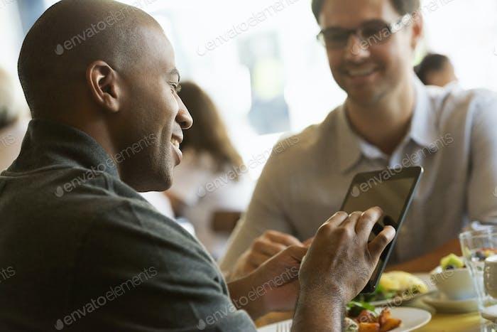 Geschäftsleute in der Stadt. Zwei Männer sitzen an einem Café-Tisch und haben eine Mahlzeit.