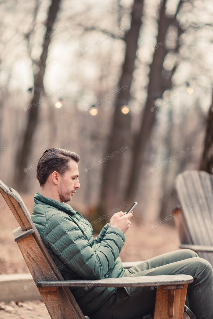 Caucasian tourist boy with cellphone outdoors in cafe. Man using mobile smartphone