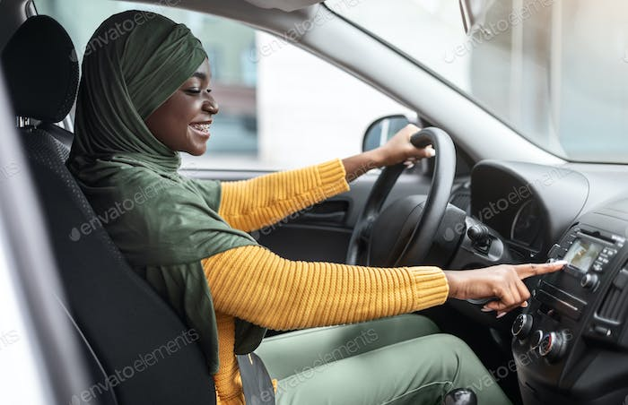 Cheerful African Muslim Woman Changing Radio Station While Listening Music In Car