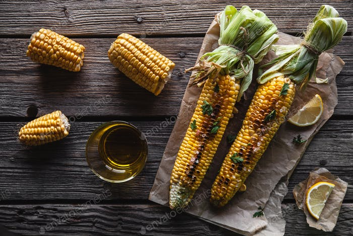 Grilled corn cobs with sauce, coriande on old wooden background. Mexican food. Top view