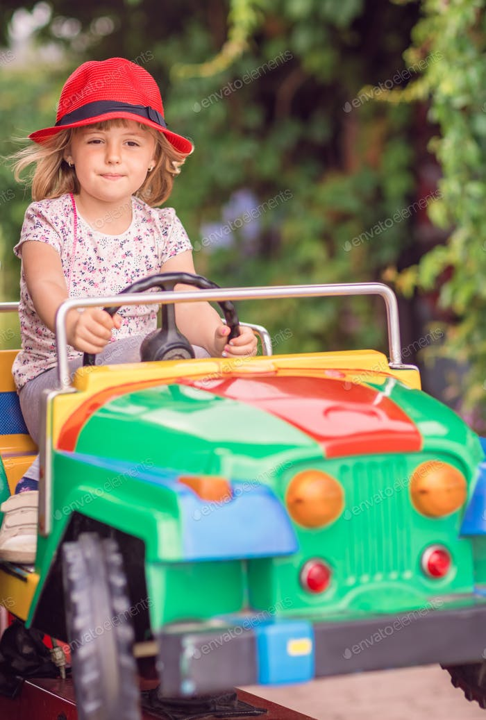 Little girl driving a toy car