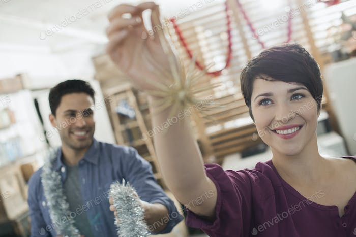 Christmas decorations. A man and woman holding tinsel and decorations.