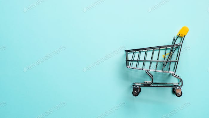Shopping cart staggered on blue, copy space