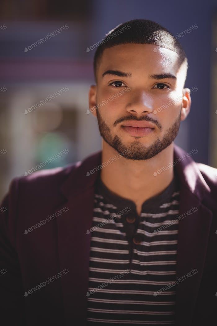 Portrait of confident young man wearing maroon blazer