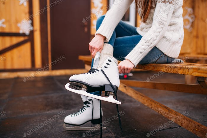 Female person sitting on bench and wears skates