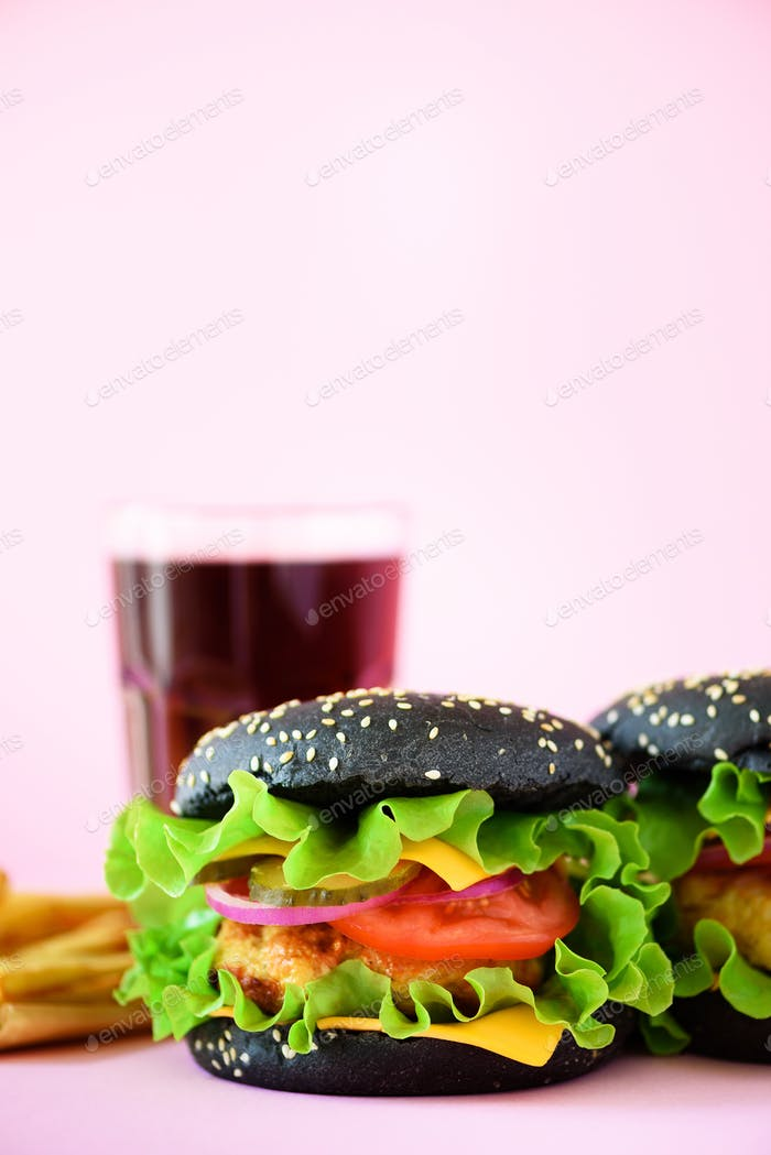 Tasty black burgers or hamburger served with french fries on pink background. Copy space. Fast food