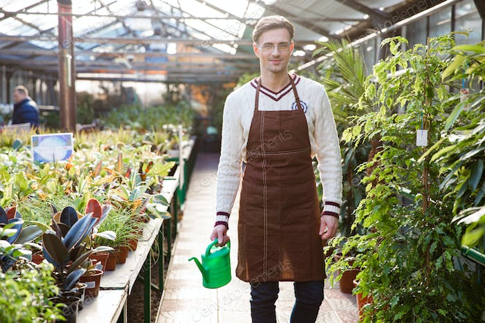 Smiling man gardener standing and holding watering can in orangery