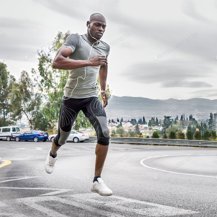 Black man running outdoors in urban road.