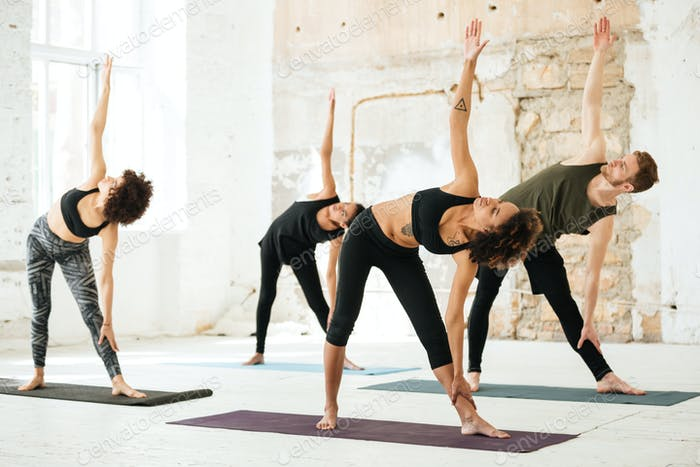 Image of young people doing yoga in gym
