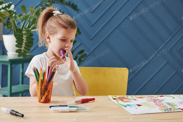 Violet marker in the mouth. Cute little girl in art school draws her first paintings