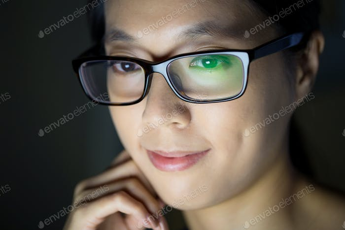 Asian woman looking at the screen at night