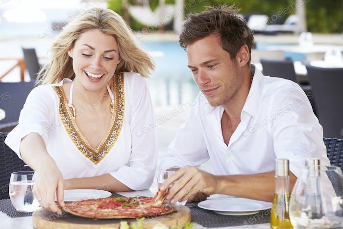 Пара наслаждаясь питанием в ресторане на открытом воздухе