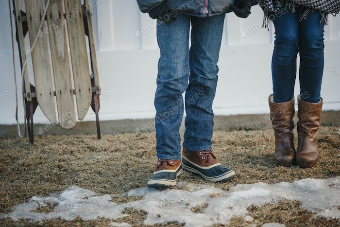 Zwei junge Leute, ein Junge und ein Mädchen stehen im Winter auf einem Hof.