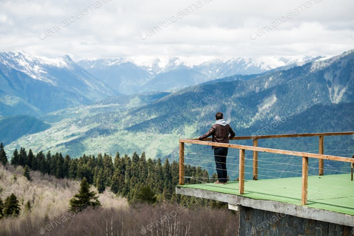 Young man in hood looking on the mountain landscape from wooden pier at morning. Rear view photo.