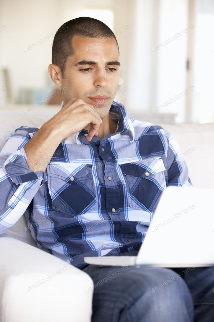 Young Man Using Laptop Computer At Home