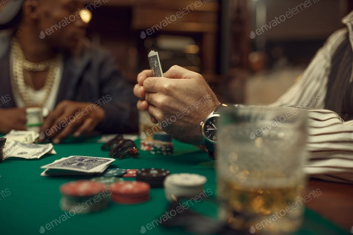 Poker players place money bets on gaming table
