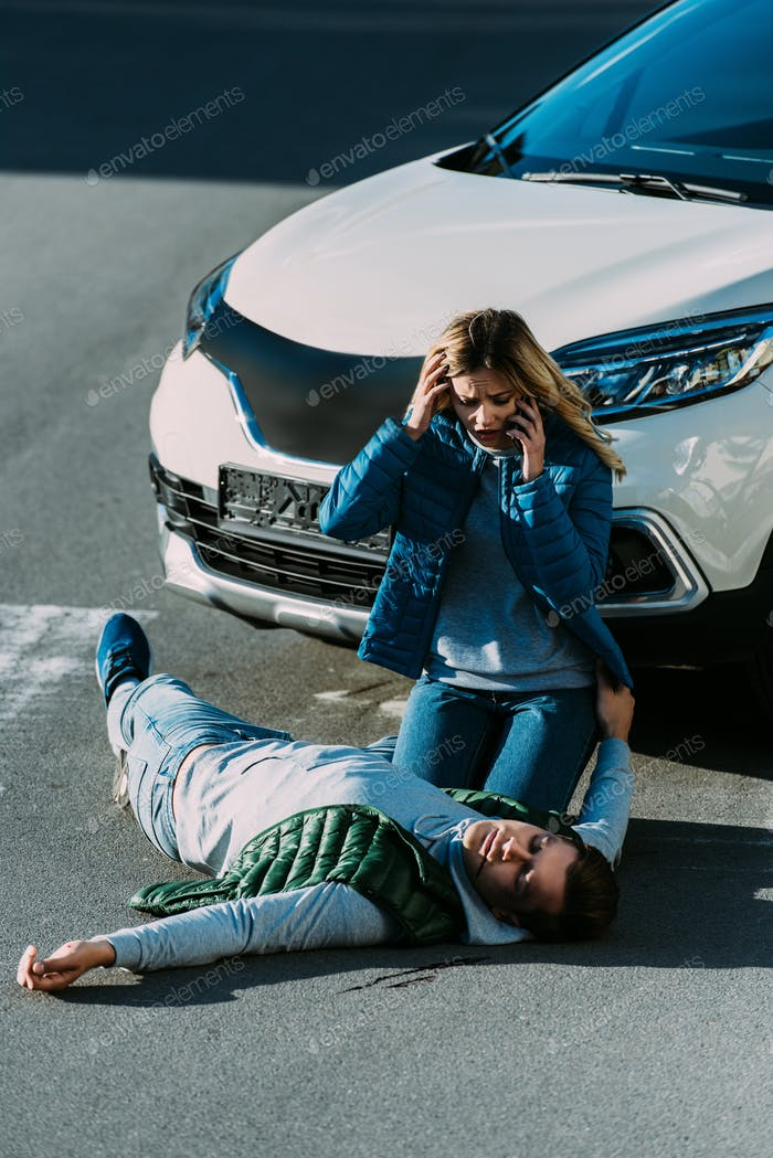 scared young woman looking at injured man and calling emergency after car accident
